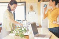 ノートパソコンのある調理台の女性2人