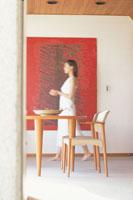 赤いタペストリー前を横切る白服女性