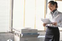 コピー機の前で書類を見る女性