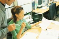 仕事デスクに座り書類を見る女性
