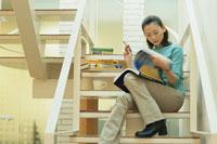 階段に座り本を読む女性