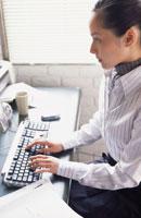 パソコンに向かうストライプのシャツの女性
