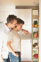 キッチンにある野菜棚を眺めるカップル