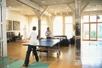 室内で卓球をする外国人カップル