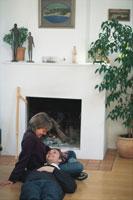 暖炉前で膝枕をして寛ぐカップル