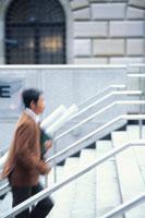 アジャスターケースを持って階段を上る日本人ビジネスマン