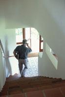 電話をしながら階段を下る男性 21069000222| 写真素材・ストックフォト・画像・イラスト素材|アマナイメージズ
