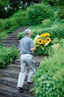ヒマワリの花を持つ男性