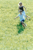 草原を走る男の子と女性