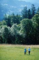 草原を歩く外国人カップル