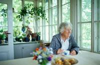 キッチンのテーブルで寛ぐ女性 21069000563| 写真素材・ストックフォト・画像・イラスト素材|アマナイメージズ