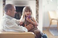 リビングルームで寛ぐ親子 21069000580F| 写真素材・ストックフォト・画像・イラスト素材|アマナイメージズ