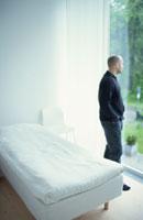 窓の外を見つめる外国人の男性 21069000689A| 写真素材・ストックフォト・画像・イラスト素材|アマナイメージズ