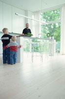 台所に立つ男性と遊ぶ子供