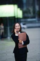 携帯電話をかける日本人OL 21069000768| 写真素材・ストックフォト・画像・イラスト素材|アマナイメージズ