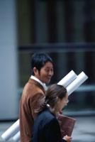 紙筒を持って歩く日本人ビジネスマンとOL