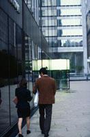 紙筒を持って歩く日本人ビジネスマンとOLの後姿 21069000773| 写真素材・ストックフォト・画像・イラスト素材|アマナイメージズ