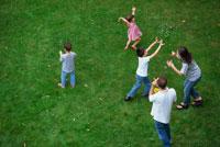 芝生の上でシャボン玉を作って遊ぶ外国人家族