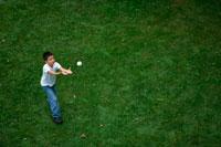 芝生の上でボールを取ろうとする外国人の男の子