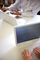 テーブルを挟んで仕事する二人 21069000787| 写真素材・ストックフォト・画像・イラスト素材|アマナイメージズ