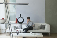白いソファに座り電話をする男性