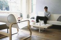 ソファでノートパソコンをする男性