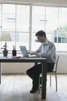 窓辺のデスクでノートパソコンを打つ男性