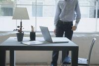 ノートパソコンのあるデスク 窓辺にたたずむ男性