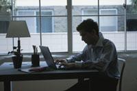 デスクでノートパソコンをする男性