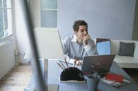 パソコンのあるデスクで肘をついて微笑む男性