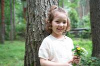 花を持って木にもたれて微笑む女の子