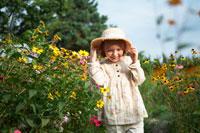 花畑で遊ぶ帽子を被った女の子