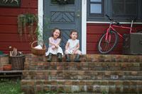 家の前の階段に座る姉妹