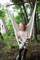 ハンモックに座る本を持った女の子