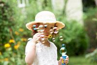 庭でシャボン玉をする女の子