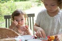 ガーデンテーブルでおやつを食べる姉妹
