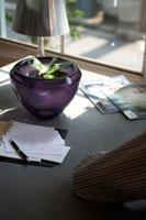 紫の花瓶のあるテーブルに男性の肘