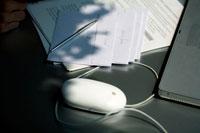 マウスや封筒などがある陽の差し込むデスク