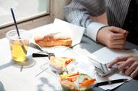 携帯電話を見ながら軽食を摂る男性の手元