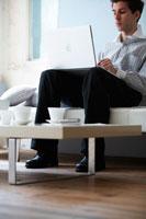 ソファでノートパソコンをする外国人男性