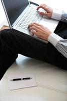 ソファに座りノートパソコンをする男性