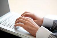 ノートパソコンのキーボードを打つ男性の手元