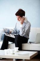 ソファに座り雑誌を見ながら電話をする男性