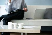 ティーセットのあるローテーブル越しのソファの男性