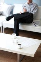 ローテーブルのコーヒーセット越しにソファの男性