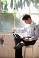窓辺のスツールに座り雑誌を見る外国人男性