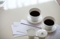 テーブルのコーヒーセットと薄紫の封筒