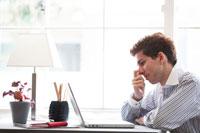 窓辺のデスクでパソコンをする男性