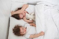 ぬいぐるみを持ってベットに横になる姉妹 21086000553C| 写真素材・ストックフォト・画像・イラスト素材|アマナイメージズ