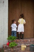木の扉を覗く2人の子供とガーデングッズ